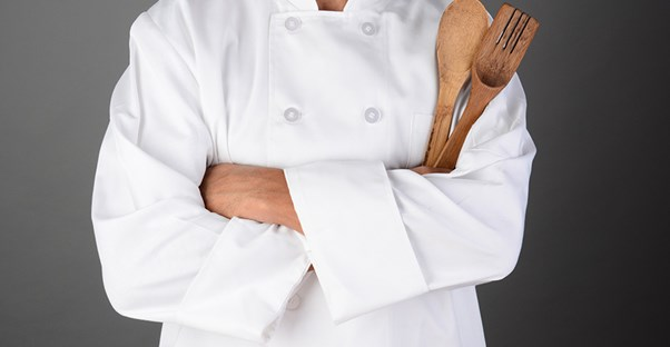A chef stands with their kitchen utensils