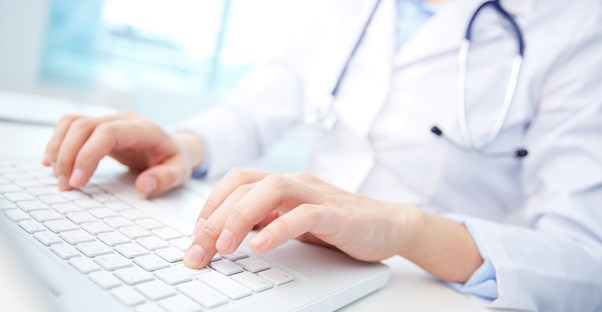 a medical transcriptionist typing up a report on a computer