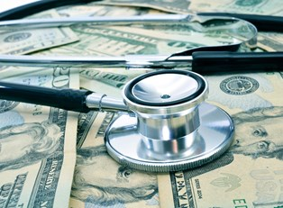 A stethoscope sitting on top of the money from a nurse practitioners salary.