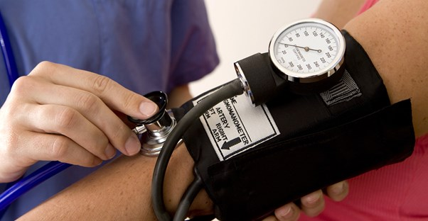 A nurse practitioner takes a patients blood pressure and thinks about the disadvantages of her job .