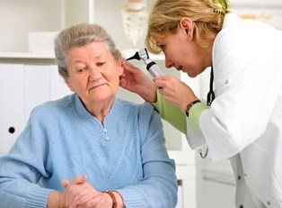An audiologist checks an elderly woman's ears
