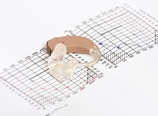 A hearing aid lies on a math problem