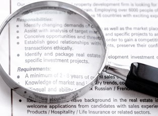 A magnifying glass lies on top of a list of requirements