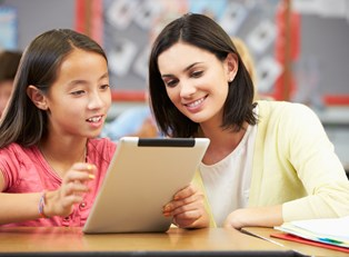 A substitute teacher shows a student something interesting on a tablet