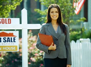 Real estate agent smiles and stands in front of a sold sign