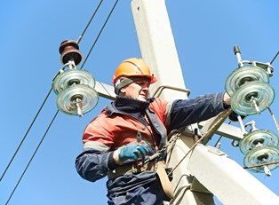 Electrician fixes broken wires on pole