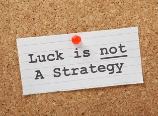 Sticky note that says Luck is not a strategy