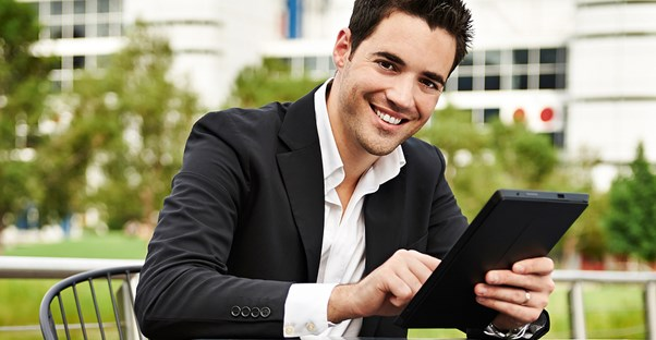 Young man smiles as he plays on his tablet