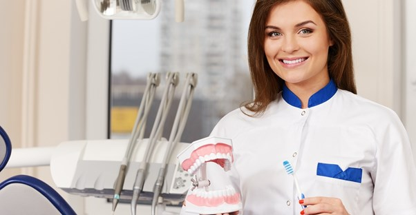 A dental hygienist holds up a toothbrush and a pair of fake teeth