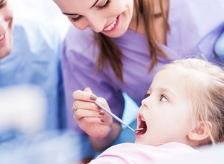 A dental hygienist checks a litle girl's teeth
