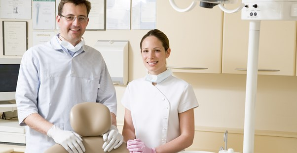 A dental hygienist and a dental assistant stand side by side in a dental office and smile at the camera