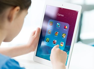 A child plays games on a tablet