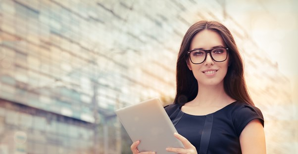 Girl with brown hair and glasses holds up a tablet