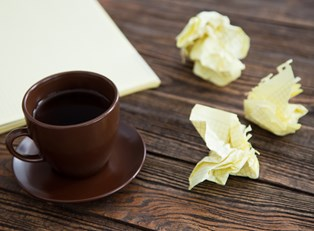 Cup of coffee with a side of crumpled notebook paper