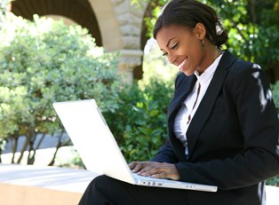 A woman smiles as she works on her laptop