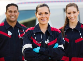 A team of EMTs stand and smile after a job well done