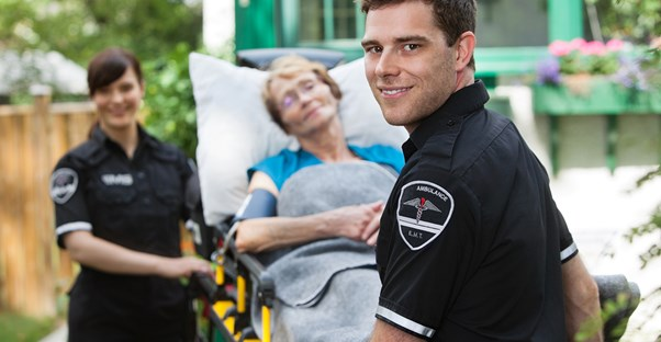 EMTs smile as they take an injured woman to the hospital on a stretcher