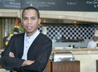A hospitality manager poses in front of a kitchen