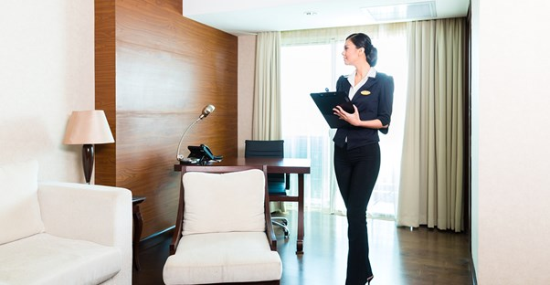 A hospitality manager inspects a hotel room