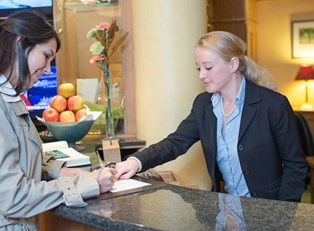 A hospitality manager checks a hotel guest in at the front desk