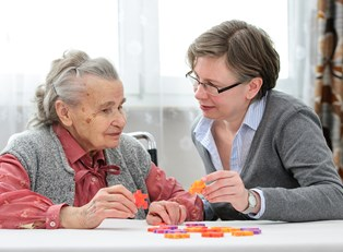 A social worker helps an elderly woman put a puzzle together