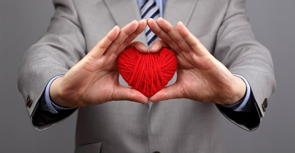 A man in a suit holds up a heart made of yarn