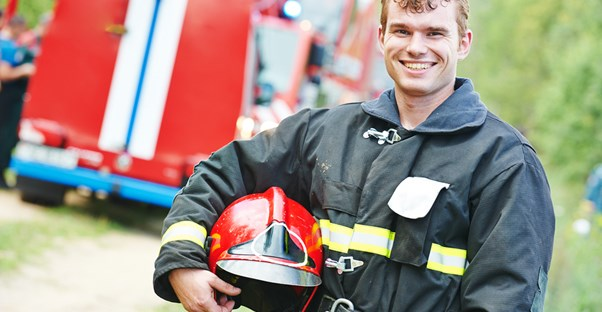 Firefighter poses with his helmet and smiles