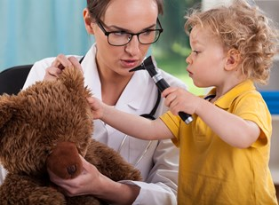 A pediatrician and a little girl play doctor with a stuffed bear