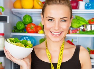 A dietitian holds up a bowl of healthy fruits and veggies