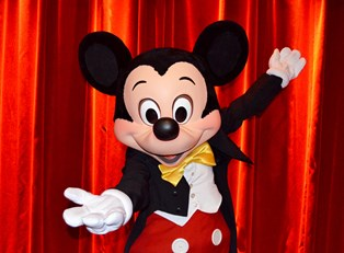 Mickey Mouse in front of a red curtain