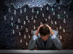 A man sits under fake rain from a fake rain cloud
