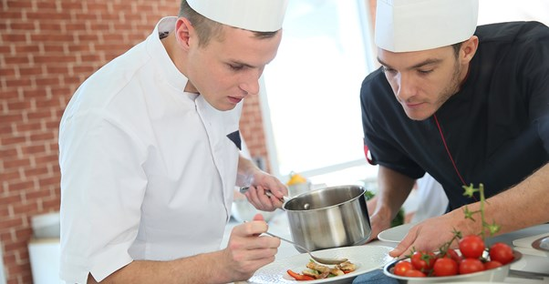A chef teaches a cook what to do in the kitchen