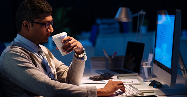A computer programmer drinks coffee during a late night of work
