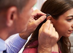 A doctor inserts a hearing aid in a young girls ear