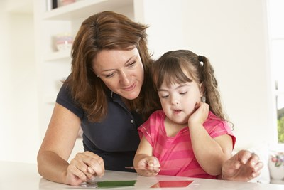 A speech pathologist works with a young girl