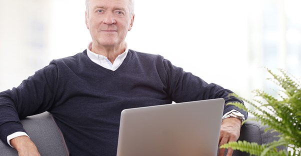 a senior citizen looking for a job on his laptop