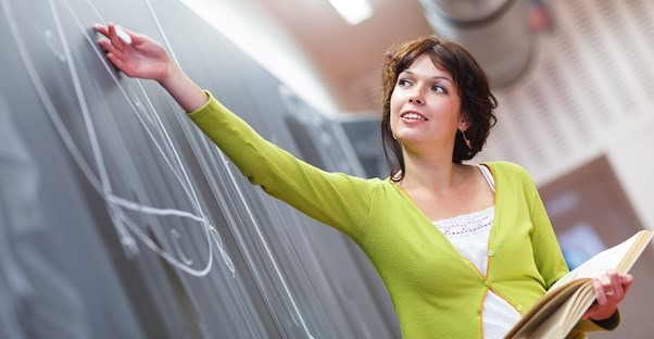 Woman in a booger-colored sweater caresses the chalk board