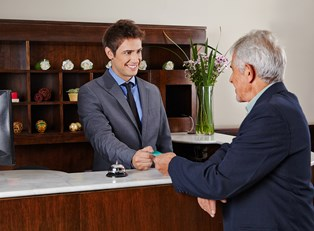 A hospitality manager gives a man his key card