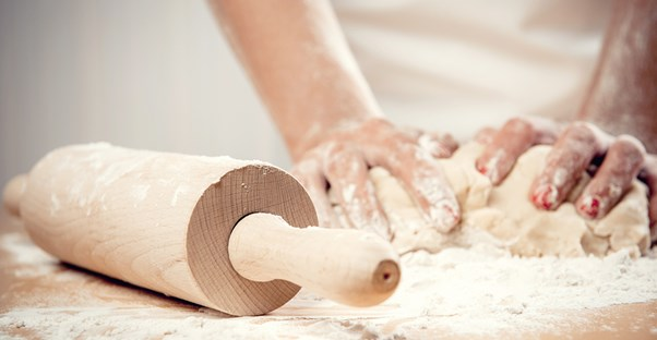 A baker kneeds dough