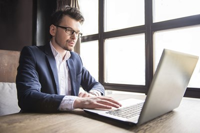 A young professional types up a work email on his laptop