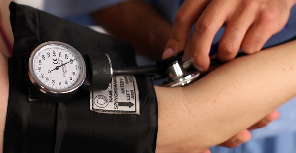 a medical assistant measuring a patient's pulse