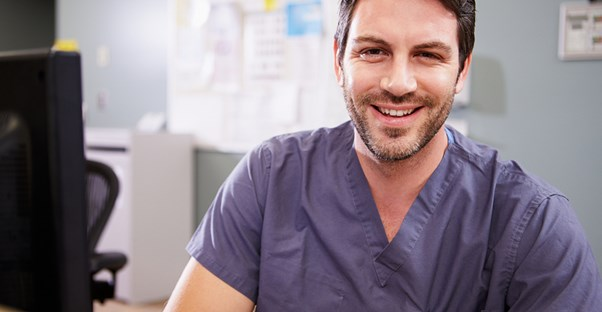 A new nurse practitioner smiles because he has finished his training and is now licensed.