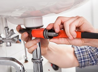 Plumber tightens with a tool