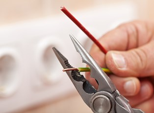 Electrician cuts a wire with a tool