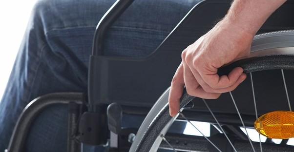 A hand rests on the wheel of a wheelchair