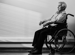 elderly man sits in a wheelchair
