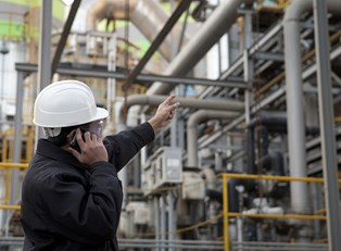 A chemical engineer talks on the phone and points to a pipe