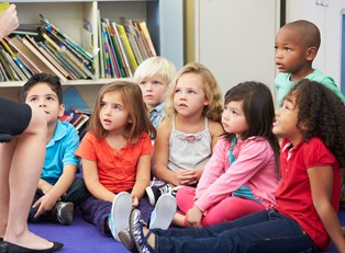 Children listen as their teacher reads them a story