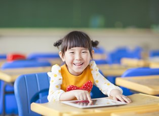 A little girl enjoys playing on her tablet