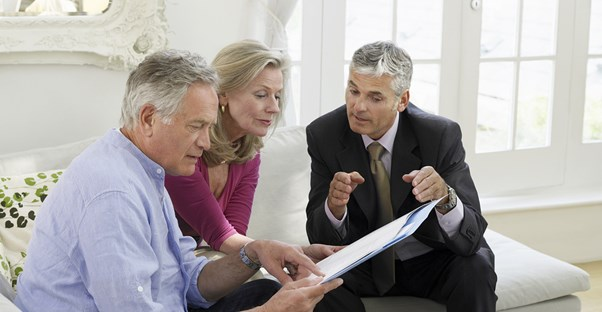 A life coach goes over some paperwork with an older couple